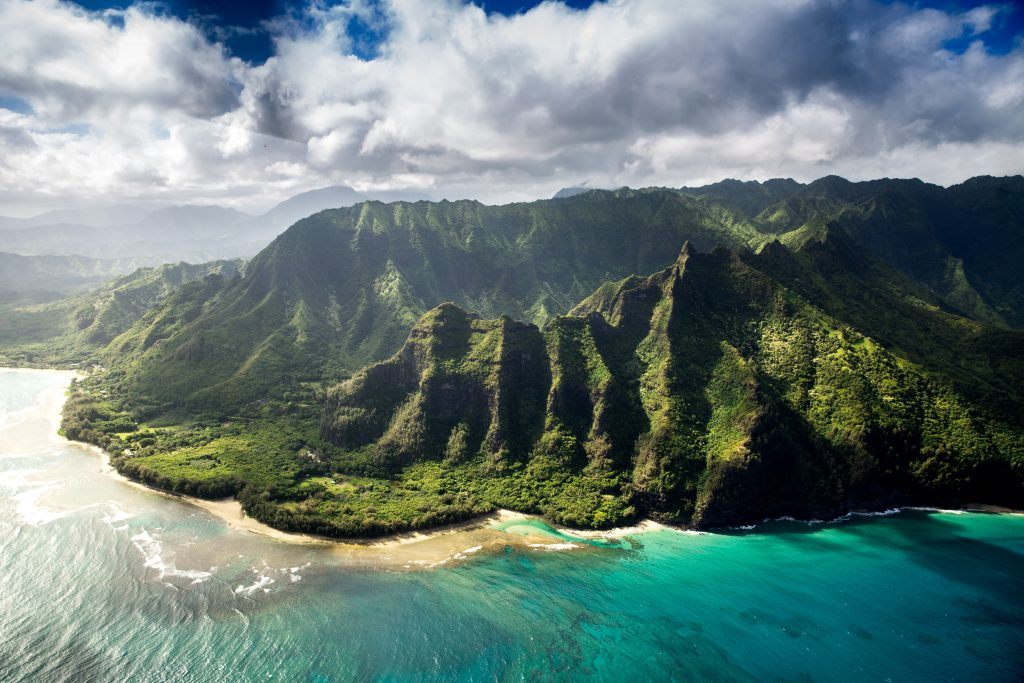Na Pali Coast in Hawaii with turquoise blue sea and green mountains making it one of the most beautiful places in the world.