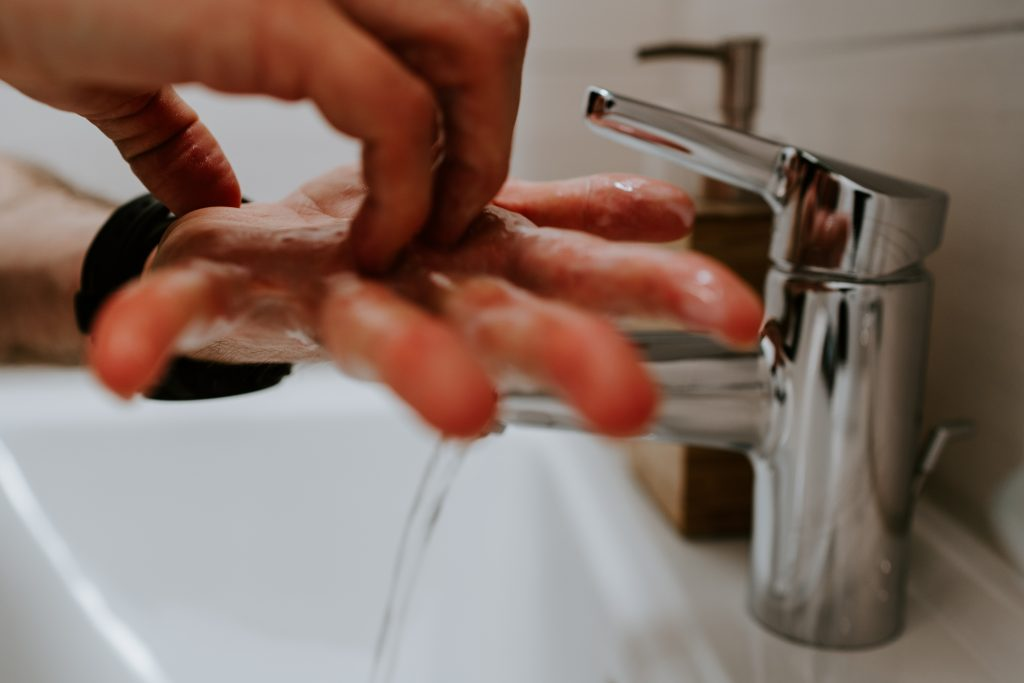 a man washing his hands in a sink.