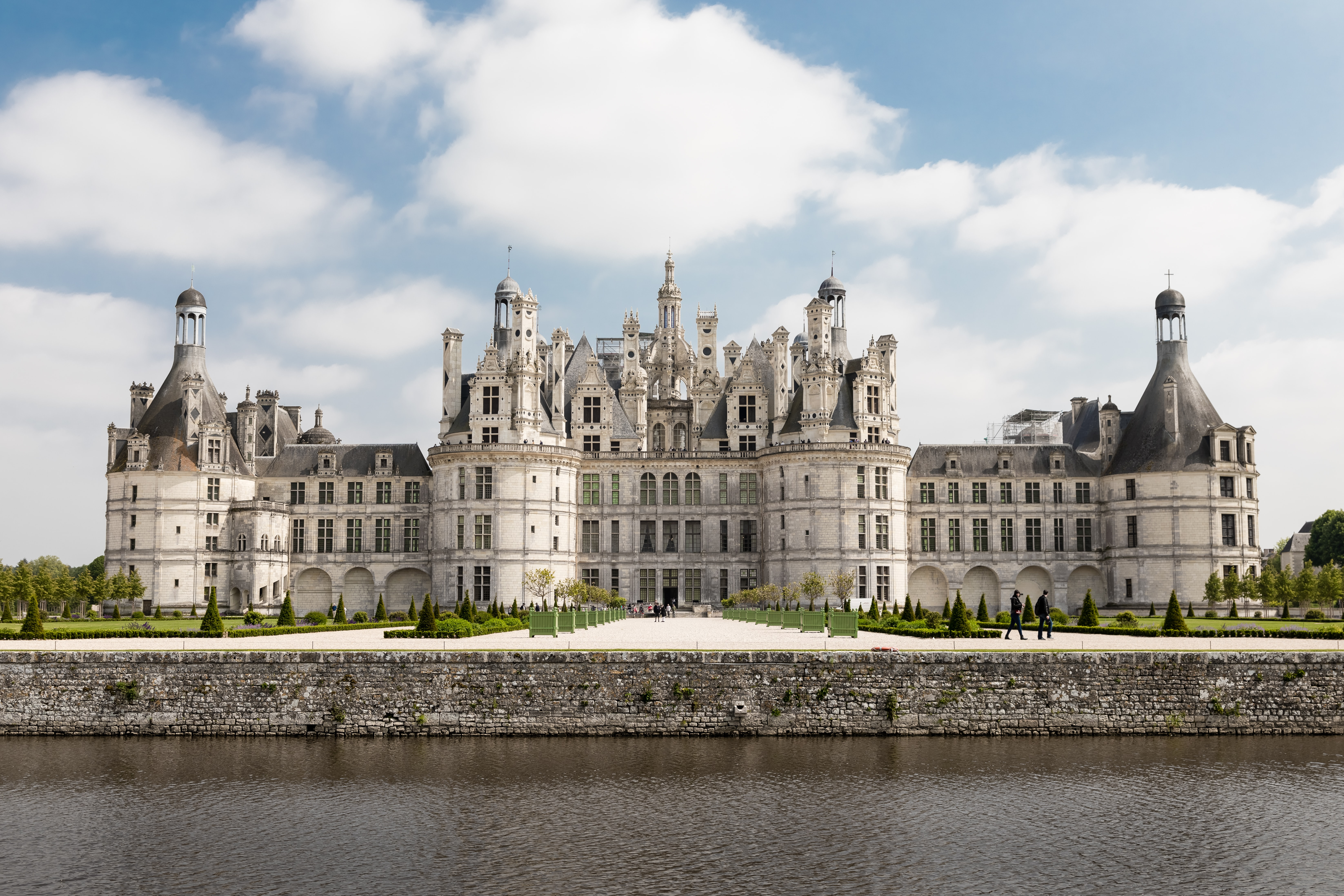 A massive white Renaissance French castle with gardens and water at the front