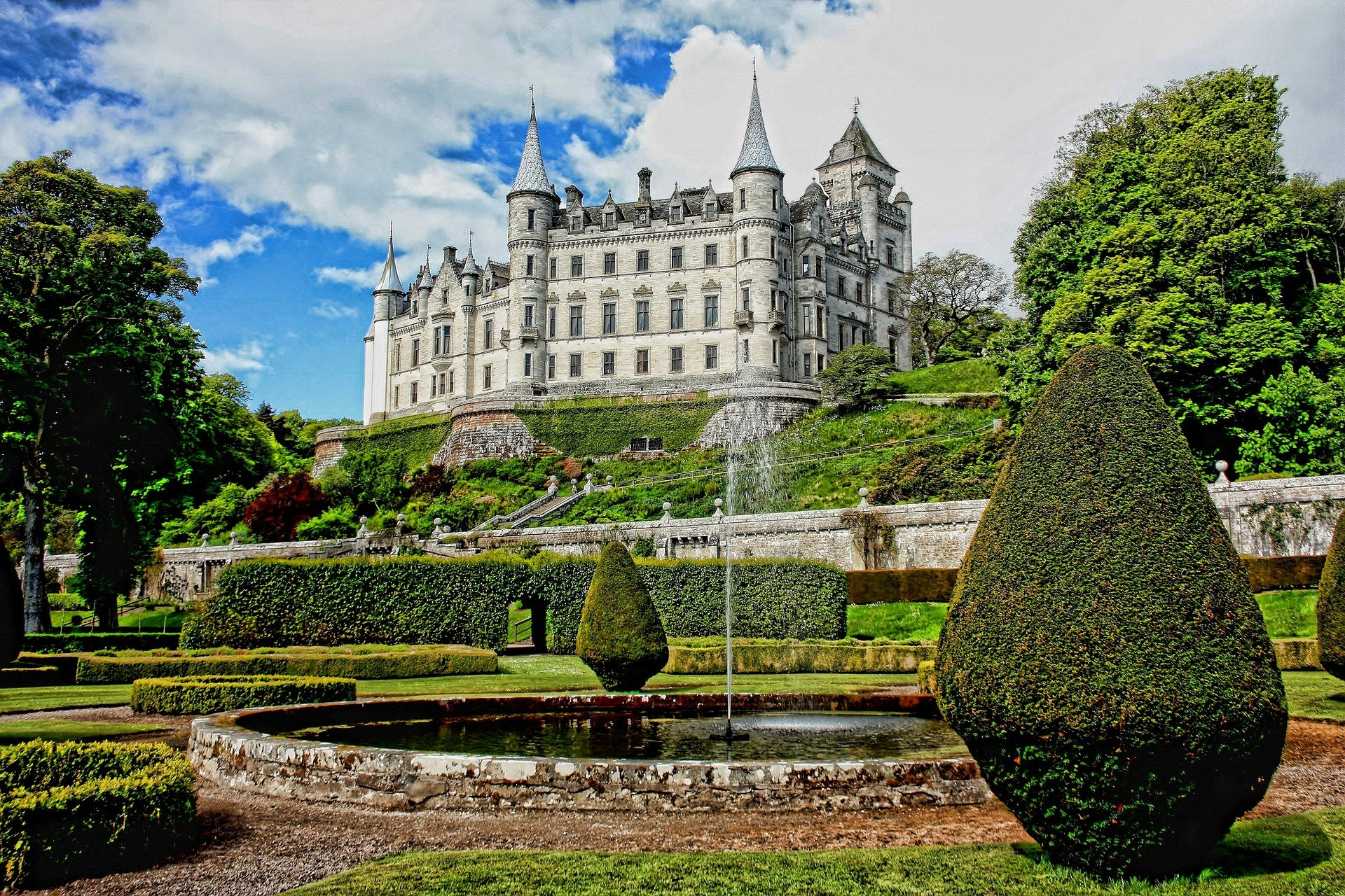 The white Dunrobin castle in Scotland with beautiful gardens in front