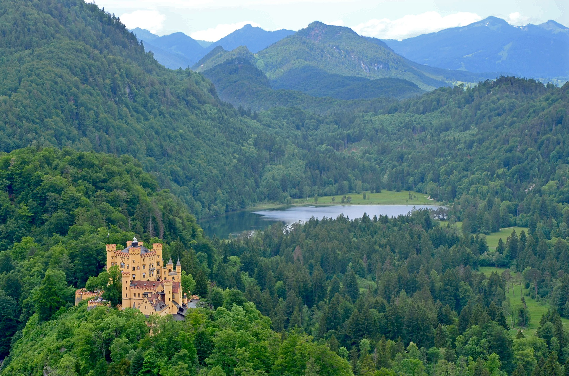 Castle in Germany surrounded by forests and hills and lake