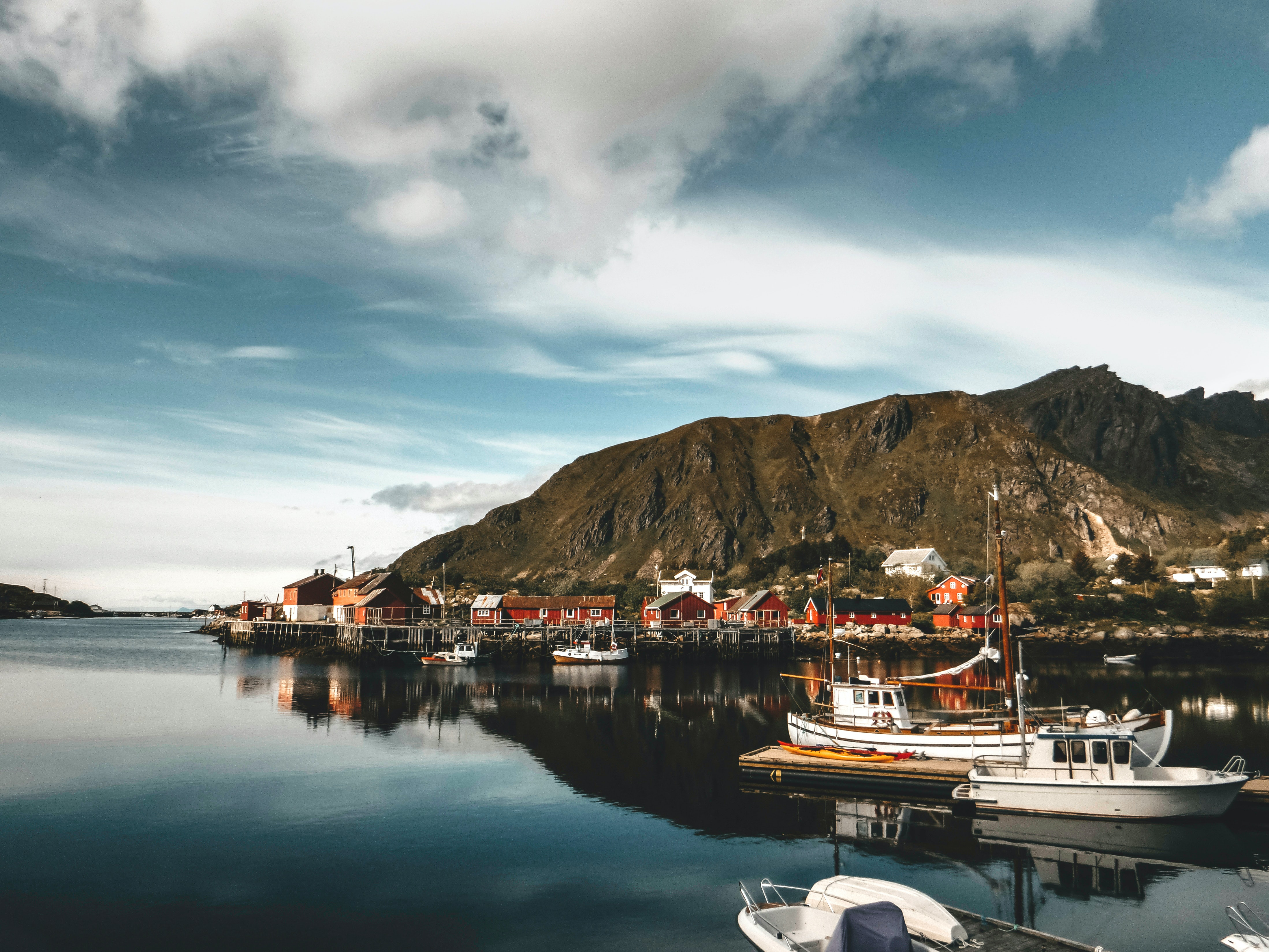 Norway is a covid alternative travel destination with fishing boats in the sea and wooden red houses.