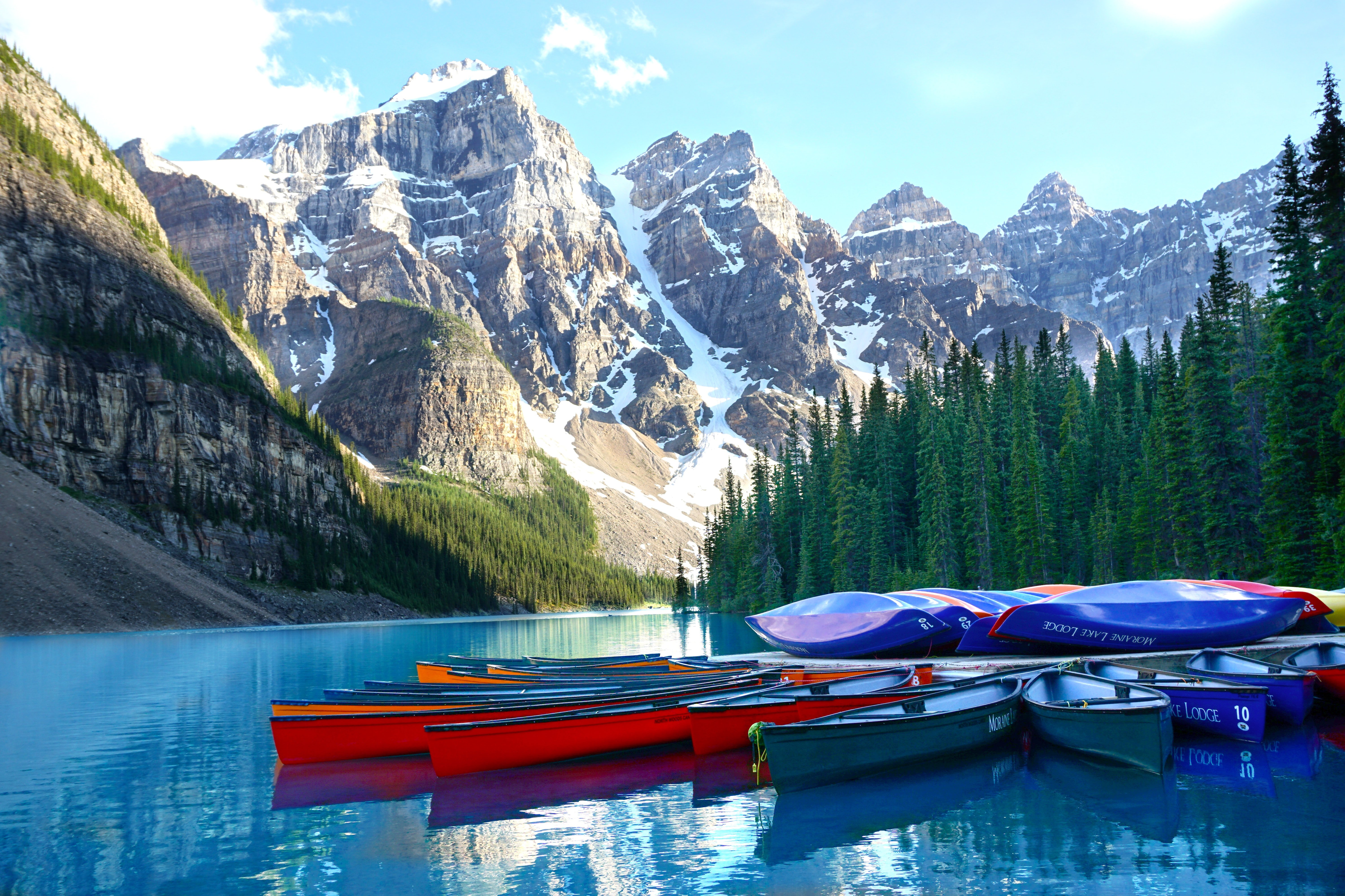 Canoes on blue waters with mountains and trees in the background