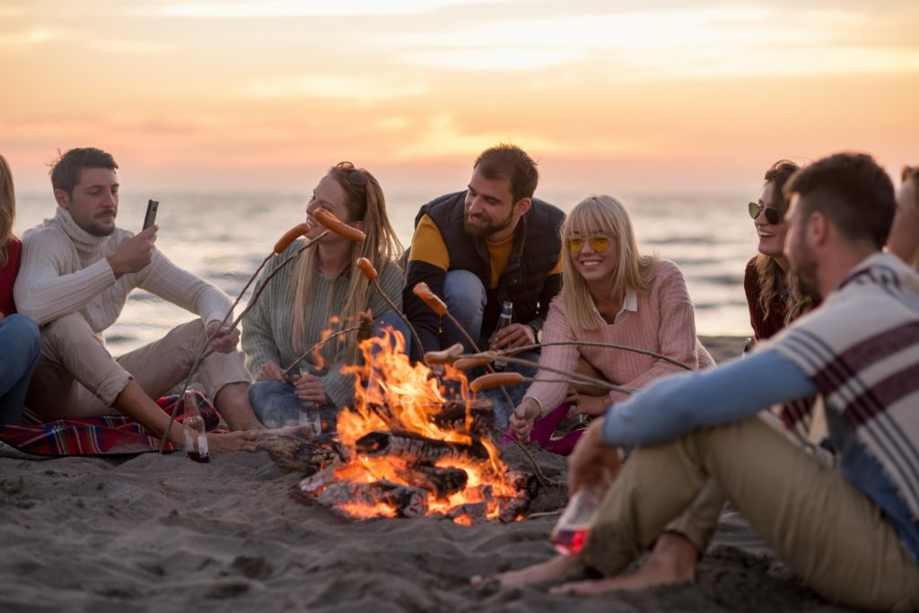 how to be the perfect trip leader people - people sat on the beach around the bonfire