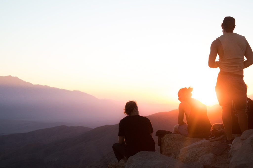 Group of people on a mountain at sunset are you an adventurer?
