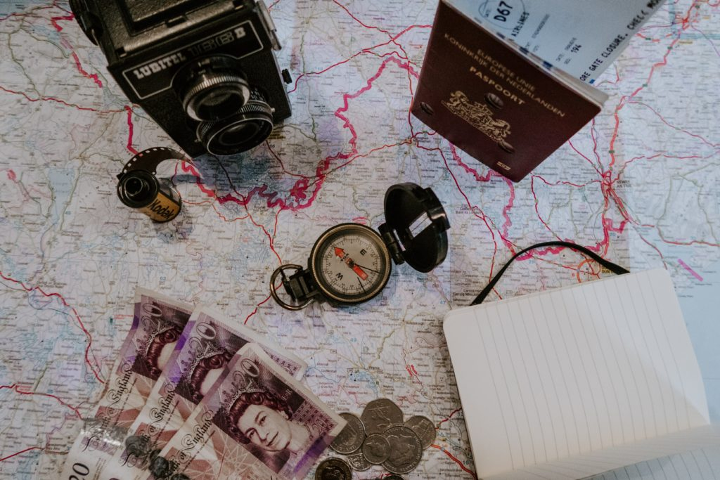 how to be the perfect trip leader - a map on a table with a passport and bank notes