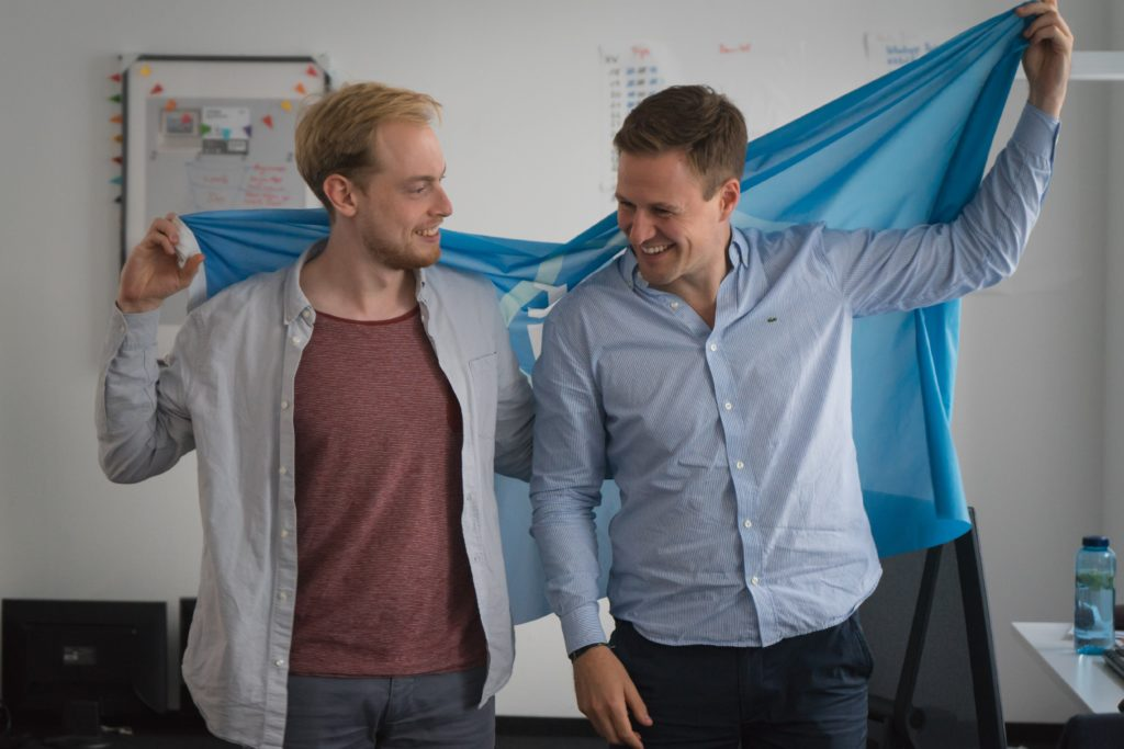 how to be the perfect trip leader the founders of join my trip holding up a flag