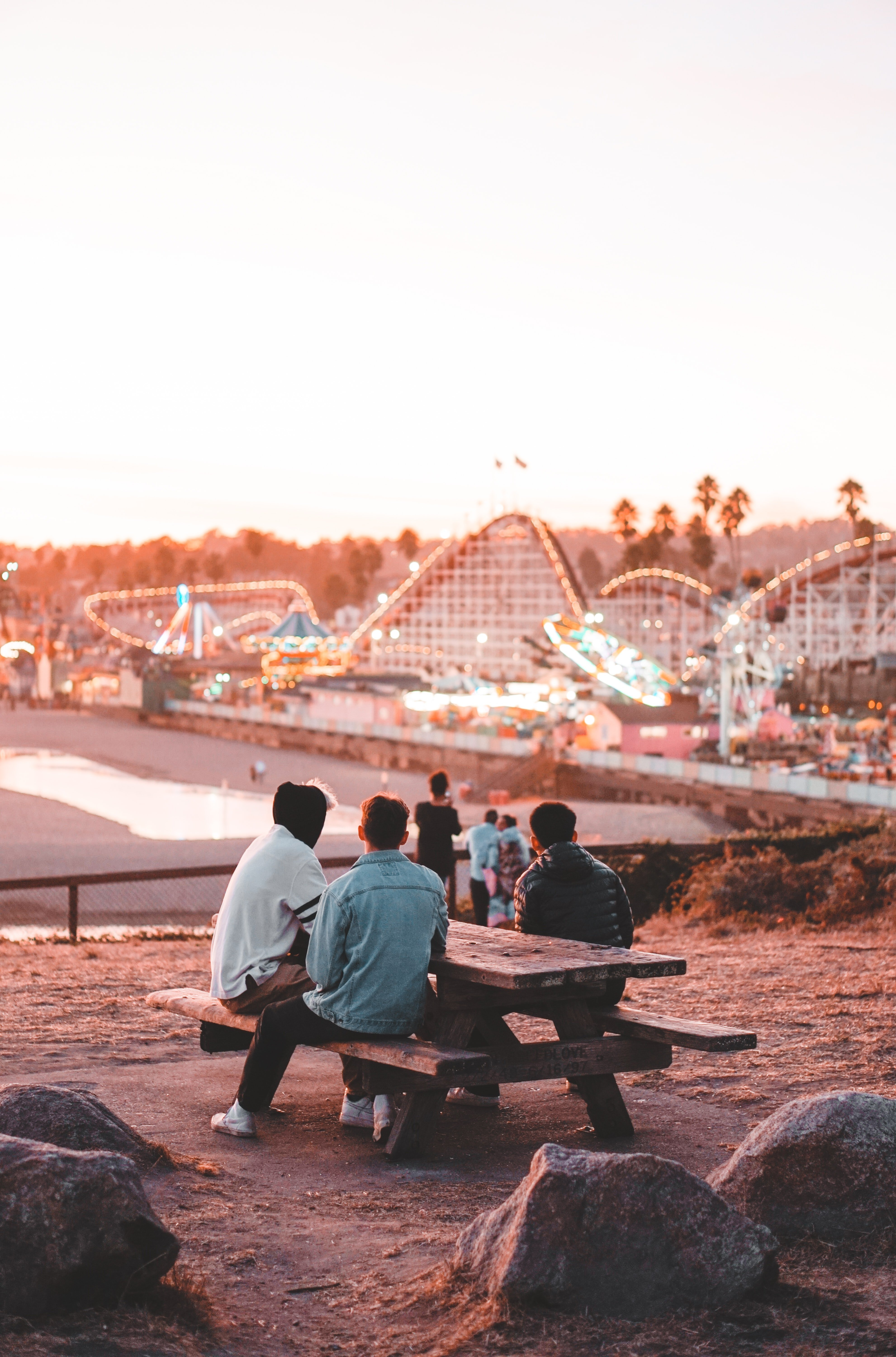 A group of friends is sitting on a bench in a theme park. In the background you can see roller coasters and other rides.