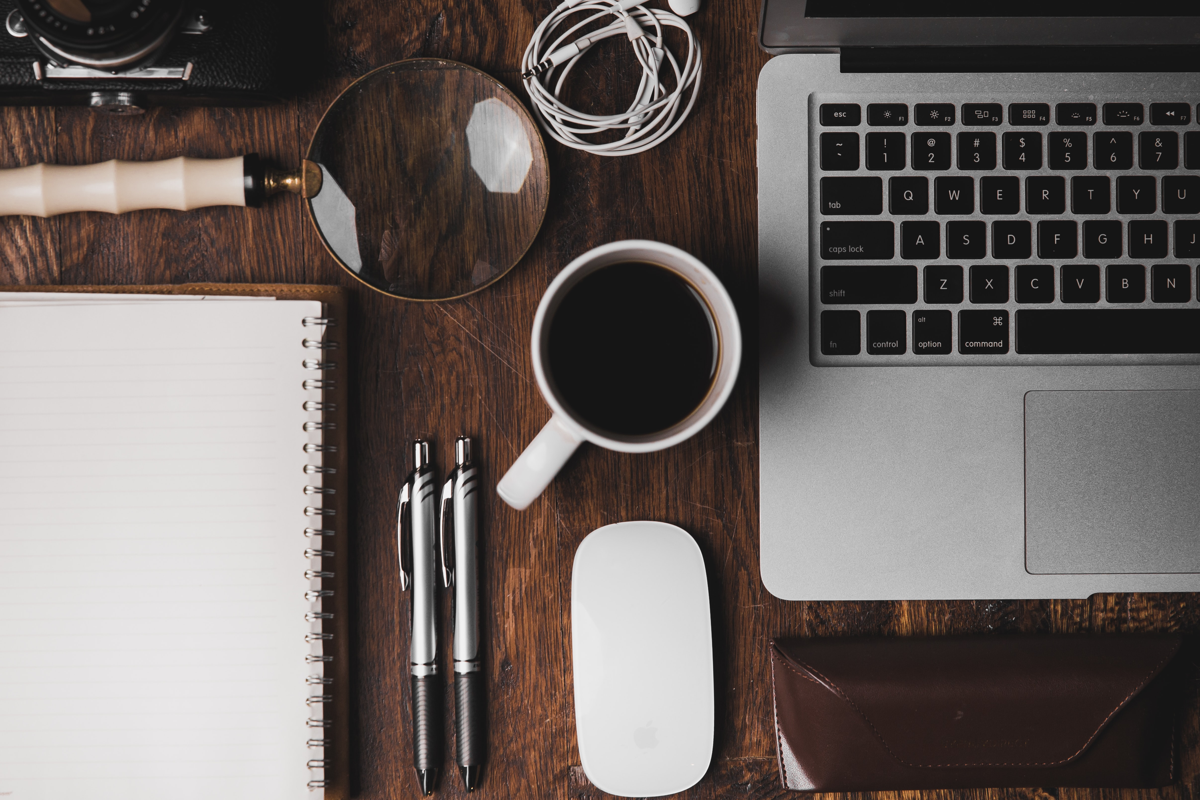 The top essentials for your coworking trip is a laptop, notebook, pens and coffee on top of a brown wooden table.